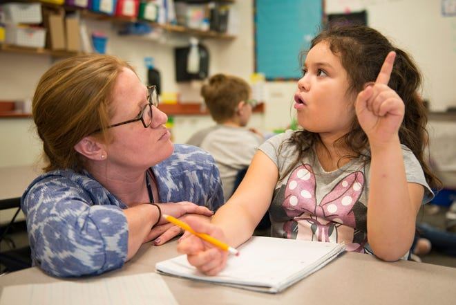 Danielle Catanzarite works with first-grader Destiny Metcalf during a writing assignment at Irish Elementary School on Tuesday, December 11, 2018. Catanzarite is a permanent substitute teacher employed with Poudre School District and fills in with daily needs at the school.