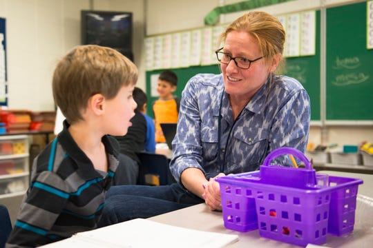 Danielle Catanzarite works with first-grader Evan Bruce during a writing assignment at Irish Elementary School on Tuesday, December 11, 2018. Catanzarite is a permanent substitute teacher employed with Poudre School District and fills in with daily needs at the school.