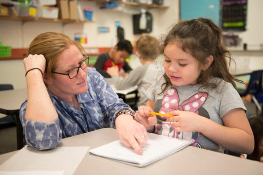 Danielle Catanzarite works with first-grader Destiny Metcalf during a writing assignment at Irish Elementary School in December.