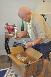 Conrad Anowski unpacks a box in his new home in Amavida.