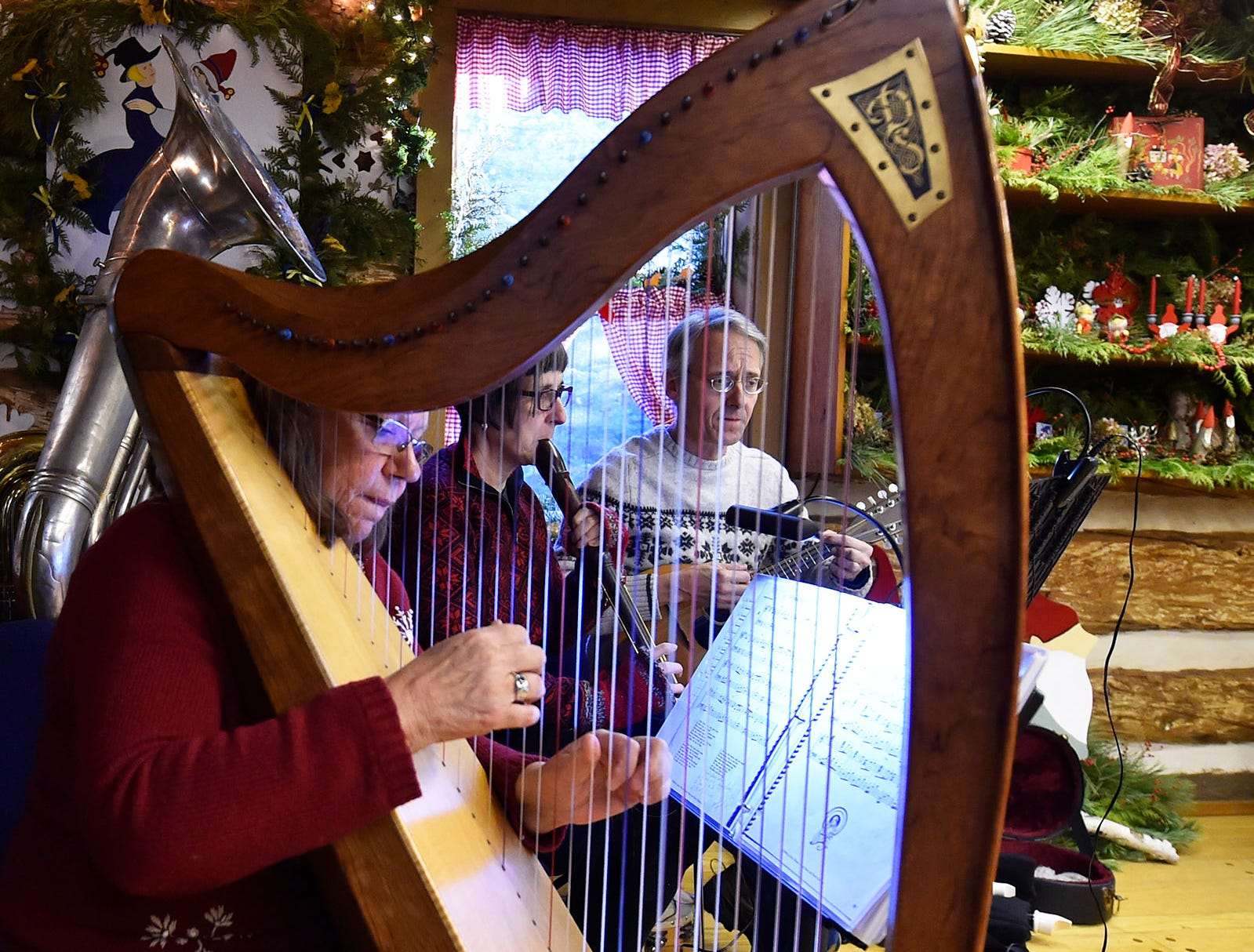 The Dusky Wing band including Dorothy Summers, from left, Vicki Medland and Mike Draney provide some of the holiday music inside Kaye Cabin during Natural Christmas at The Ridges Sanctuary, 8166 State 57, Baileys Harbor. Tina M. Gohr/USA TODAY NETWORK-Wisconsin