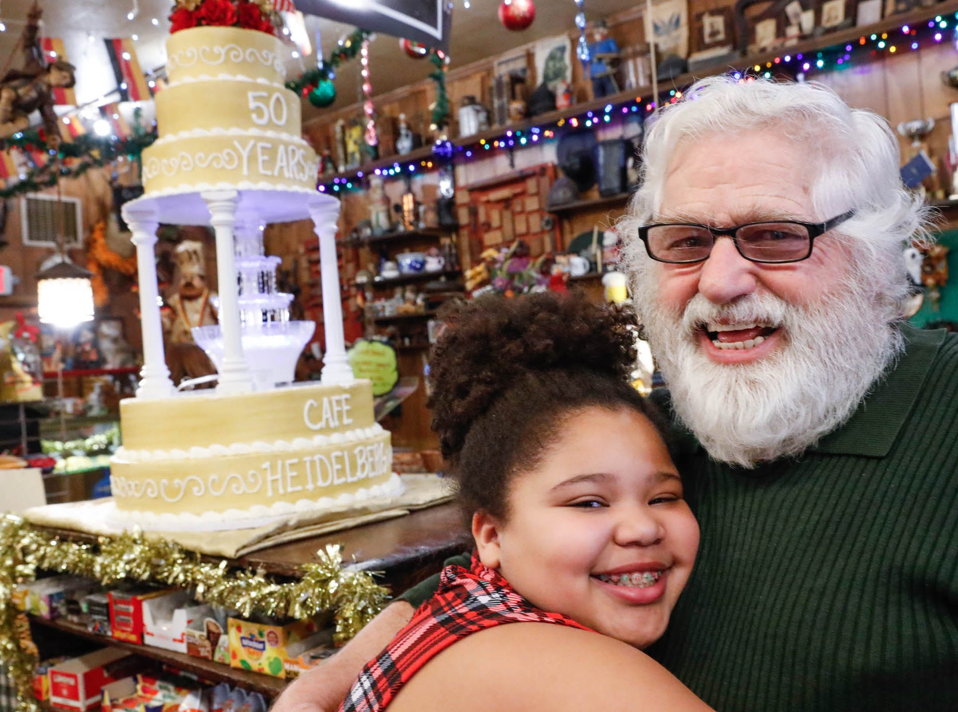 "Heidelberg Haus Cafe and Bakery owner Juergen ""JJ"" Jungbauer hugs his granddaughter Mattea Ugoletti during a party celebrating the cafe's 50th year in business, on Saturday, Dec. 8th, 2018. The cafe, bakery, and German grocery is well known for its extensive collection of German Kitsch."
