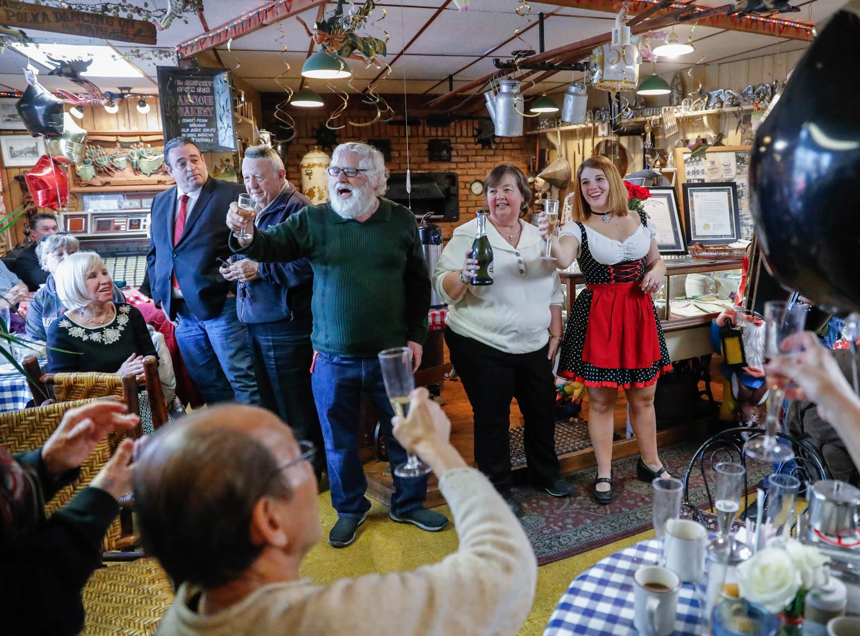 "Heidelberg Haus Cafe and Bakery owners Juergen ""JJ"" Jungbauer, left, his wife Gabi, and their daughter Angela Corkwell, lead guests in a song during a party celebrating the Cafe's 50th year in business on Saturday, Dec. 8th, 2018. The couples family and regular customers were on hand for the celebration."