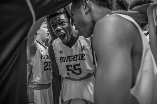 Riverside Argonauts' Emmanuel Gbeyor (55) cheers with teammates in a huddle before the start of their game against the Lighthouse South Bulldogs at Riverside High School in Indianapolis on Tuesday, Dec. 4, 2018.