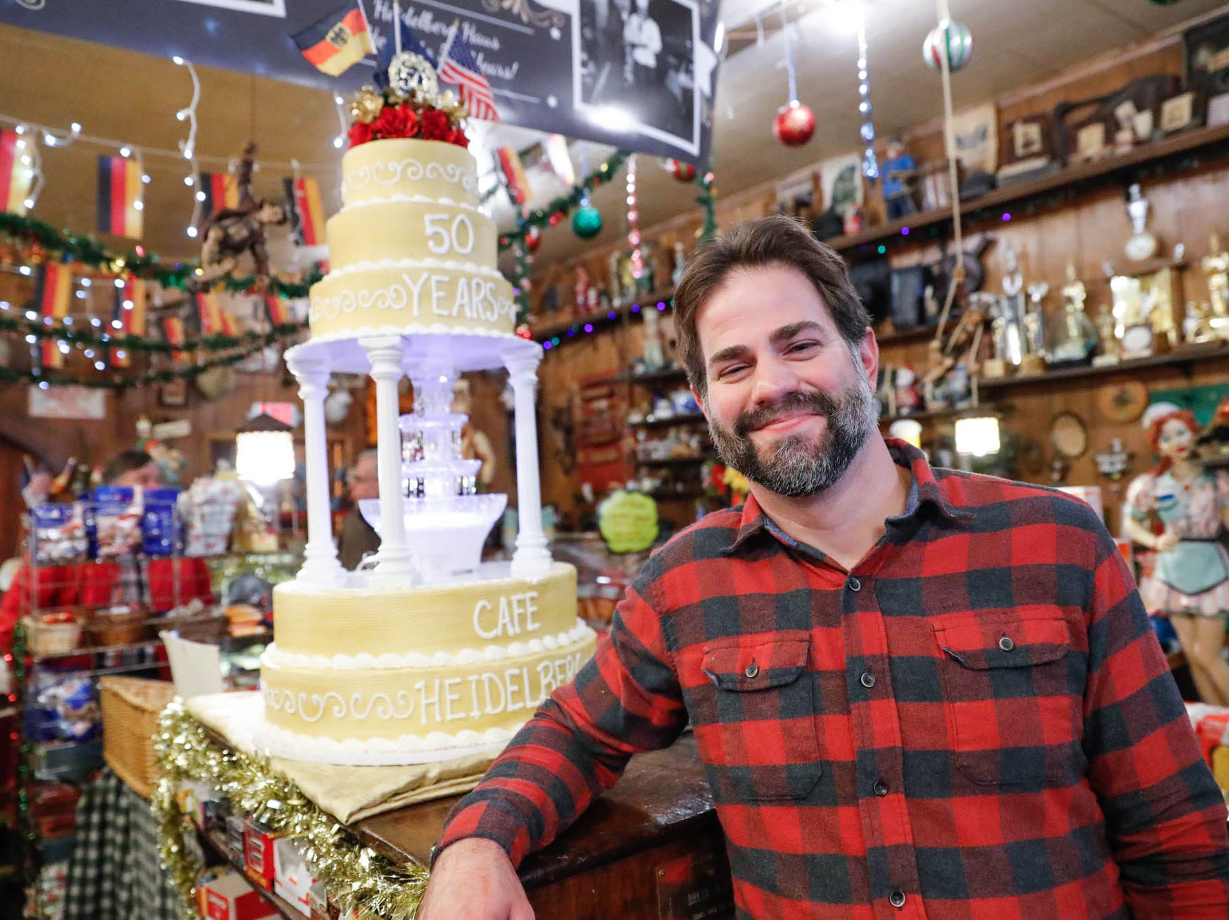 Pastry Chef Charles Corkwell stands by the Heidelberg Haus cake he created to celebrate the cafe's 50th year in business, during a party with guests and regulars, at Heidelberg Haus Cafe and Bakery,7625 Pendleton Pike, Indianapolis Ind., on Saturday, Dec. 8th, 2018. The cafe, bakery, and German grocery are well known for its extensive collection of German Kitsch and baked goods.