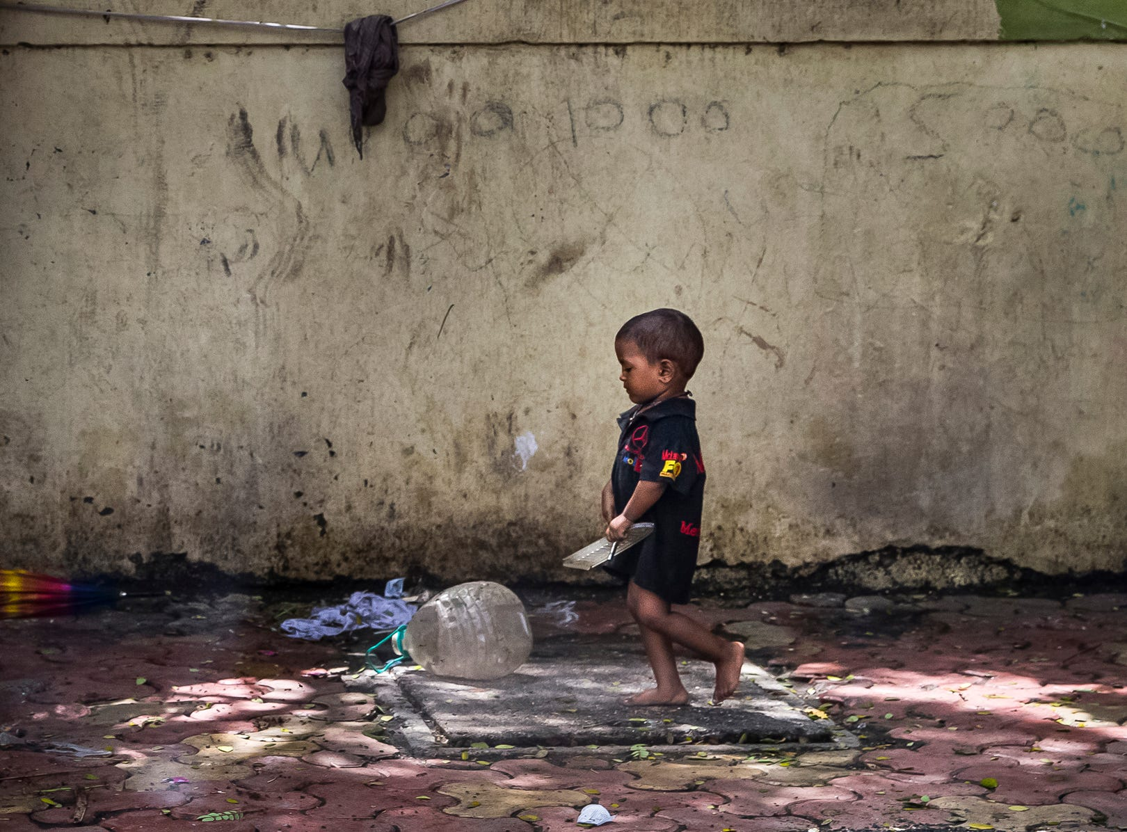 A young child walks along a sidewalk near a makeshift hut in Mumbai, India.