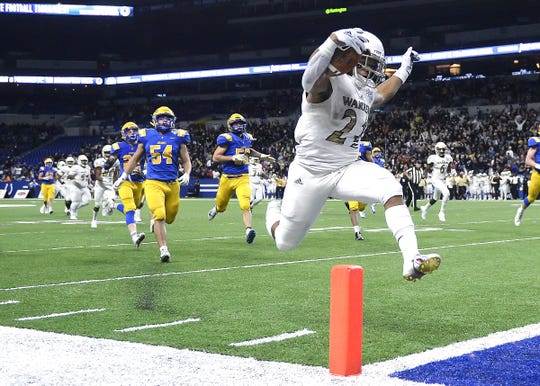 Warren Central's Romeir Elliott (21) scores a touchdown against Carmel in the first half of the IHSAA Class 6A state final game at Lucas Oil Stadium in Indianapolis, Ind., Friday, Nov. 23, 2018.