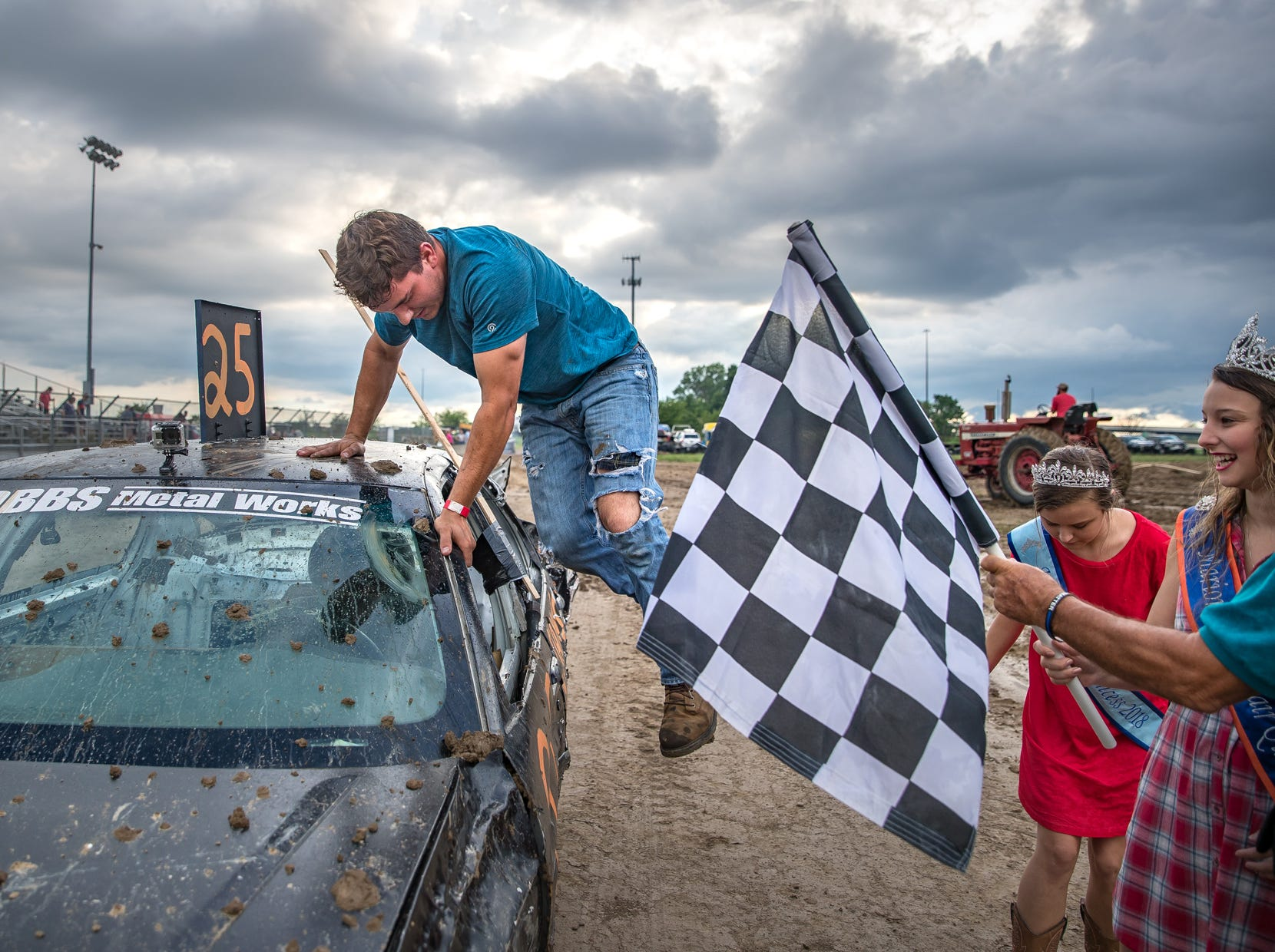 "Cole Whoton jumps out of his car after winning night one of demolition derby action at the Marion County Fair on Friday, June 22, 2018. ""It felt great to win,"" he said. ""I love seeing the crowd go wild."" After exiting the car he worked on with his father, Clayton, who also participated in the derby, Fair Queen Paige Wells, a senior at Butler University, hands him the checkered flag."