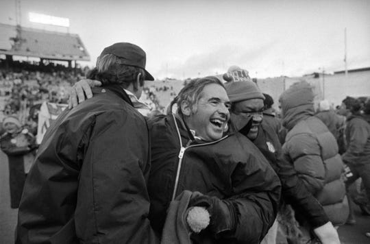 Notre Dame head football coach, Dan Devine, wears a big smile as he embraces an unidentified assistant coach from University of Houston in the Cotton Bowl Monday, January 1, 1979 after his Fightin' Irish team defeated University of Houston in final seconds 35-34.