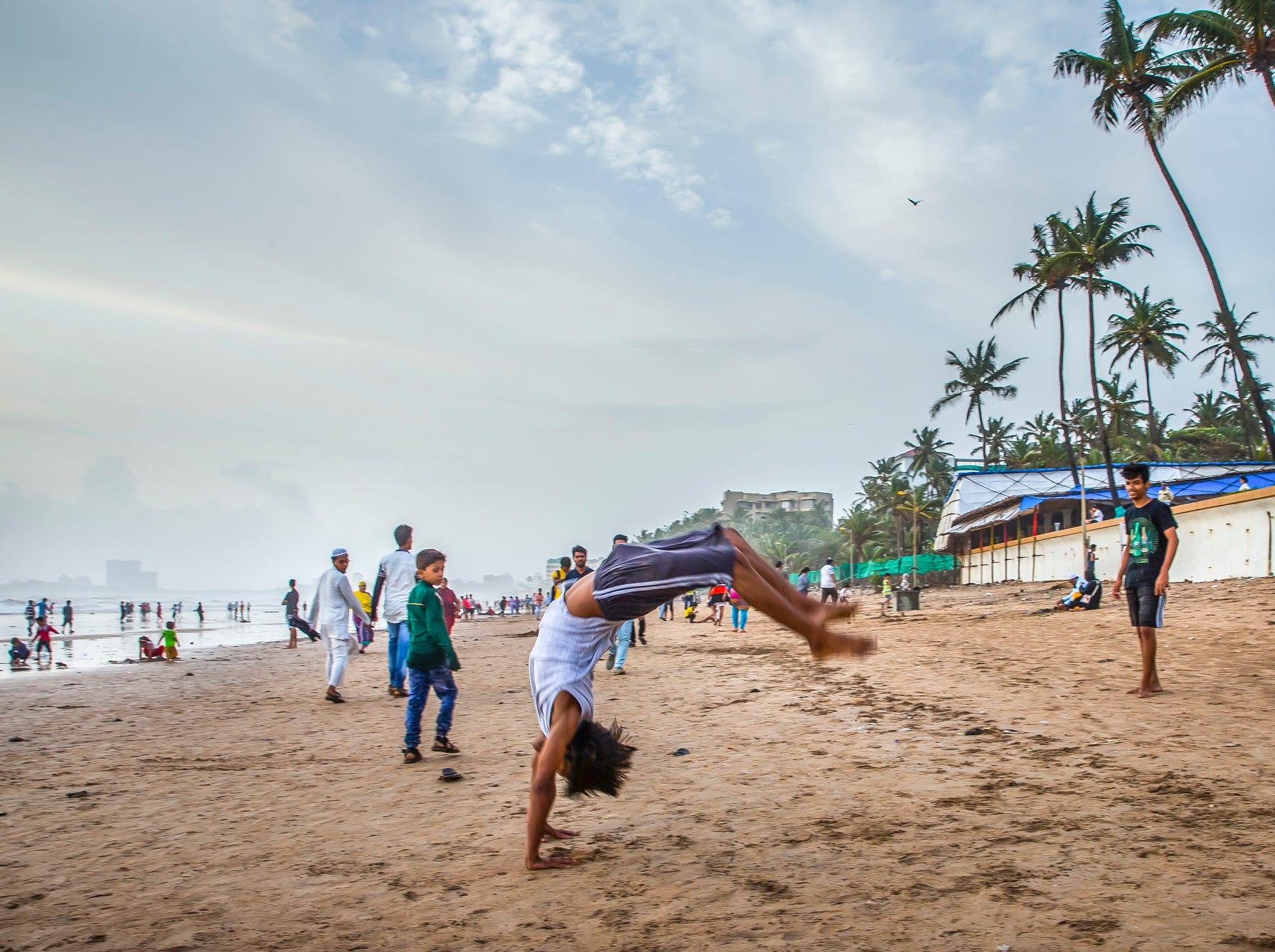 During a break in the monsoon rains, Salman Khan, 17, flips down Juhu Beach in Mumbai, India.