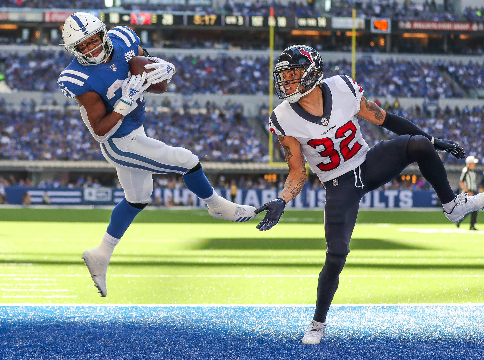 Indianapolis Colts running back Nyheim Hines (21) goes up and over Houston Texans defensive back Tyrann Mathieu (32) for the touchdown grab at Lucas Oil Stadium on Sunday, Sept. 30, 2018.
