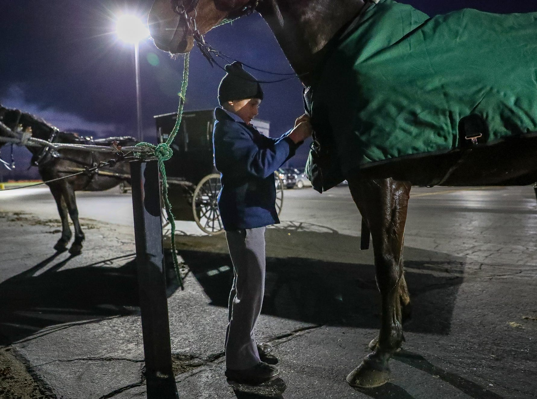 Galen Bontrager, 13, puts a coat on his horse, Bobby, after arriving to Westview High School in Topeka, Ind., to watch the Warriors take on the Bethany Christian Bruins in basketball on Tuesday, Nov. 20, 2018.