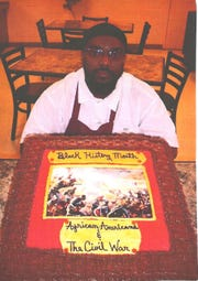 Prison inmate Antonio Barnes poses with one of his cakes celebrating Black History Month.