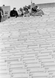 Some loyal University of Houston fans brave the 20-degree, 15-to-20 mile per hour winds from the northwest to watch their Cougars do battle with the Irish of Notre Dame in the Cotton Bowl in Dallas, Texas, Jan. 1, 1979. Empty seats prove there were many not-so-hearty souls who remained indoors and watched the game on television.