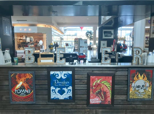 Signs from breweries supported by Iowa Beer Crafts and Drafts kiosk inside the Coral Ridge Mall are shown on Dec. 11, 2018.
