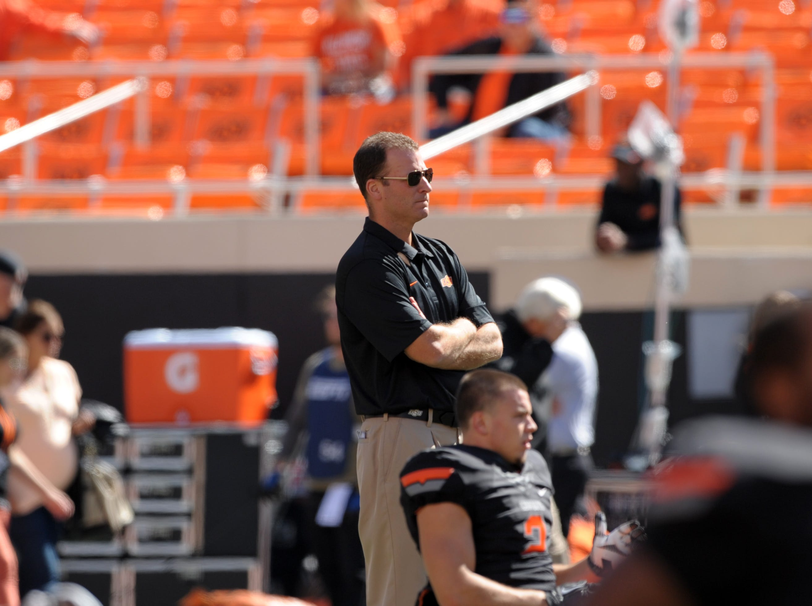 First year Oklahoma State offensive coordinator Mike Yurcich, watches warm-ups before an NCAA football game in Stillwater, Okla., Saturday, Oct. 5, 2013. Oklahoma State defeated Kansas State 33-29.
