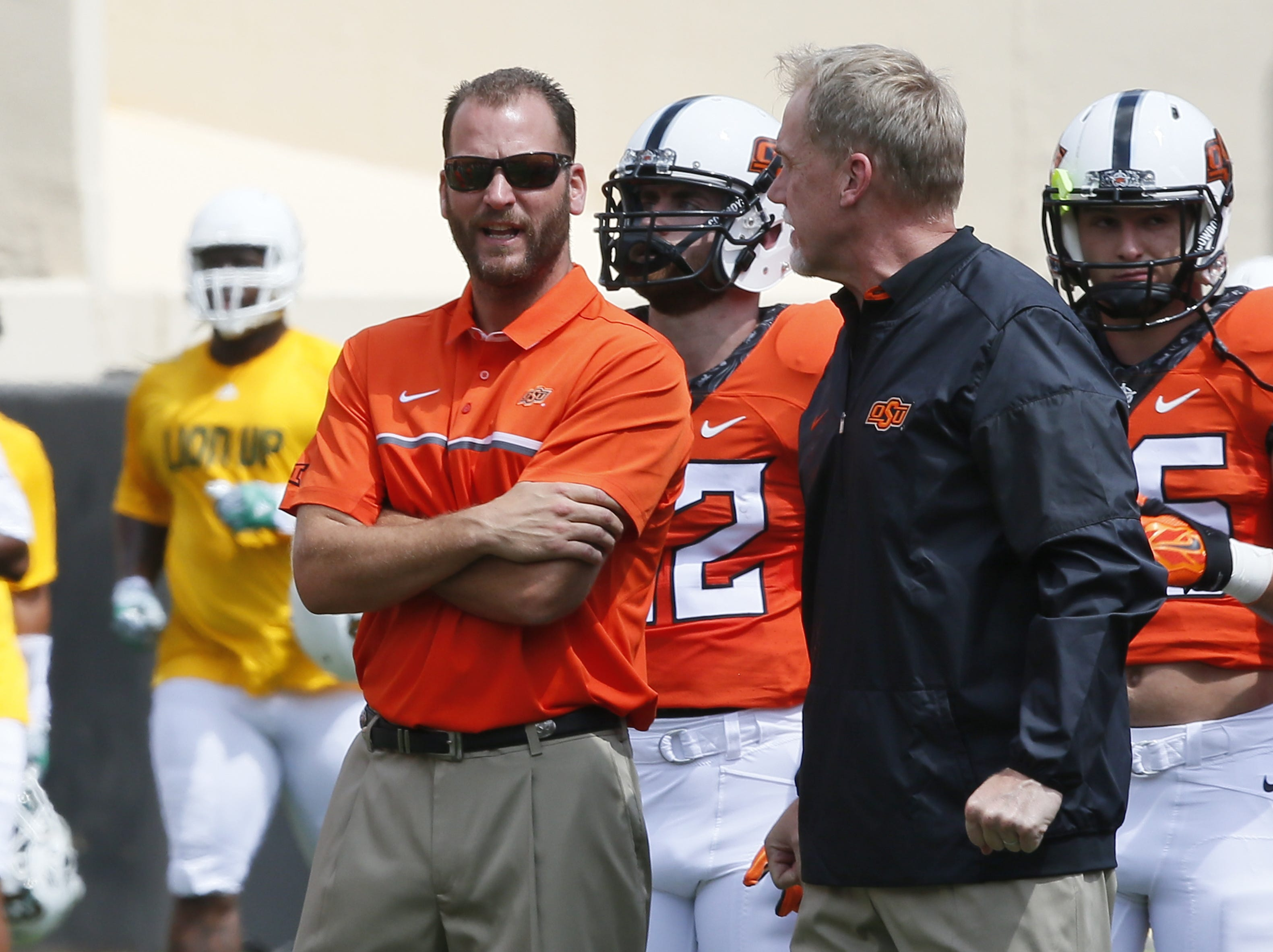In this Saturday, Sept. 3, 2016 photo, Mike Yurcich, left, Oklahoma State offensive coordinator, talks with Glenn Spencer, right, defensive coordinator, before an NCAA college football game against Southeastern Louisiana in Stillwater, Okla.