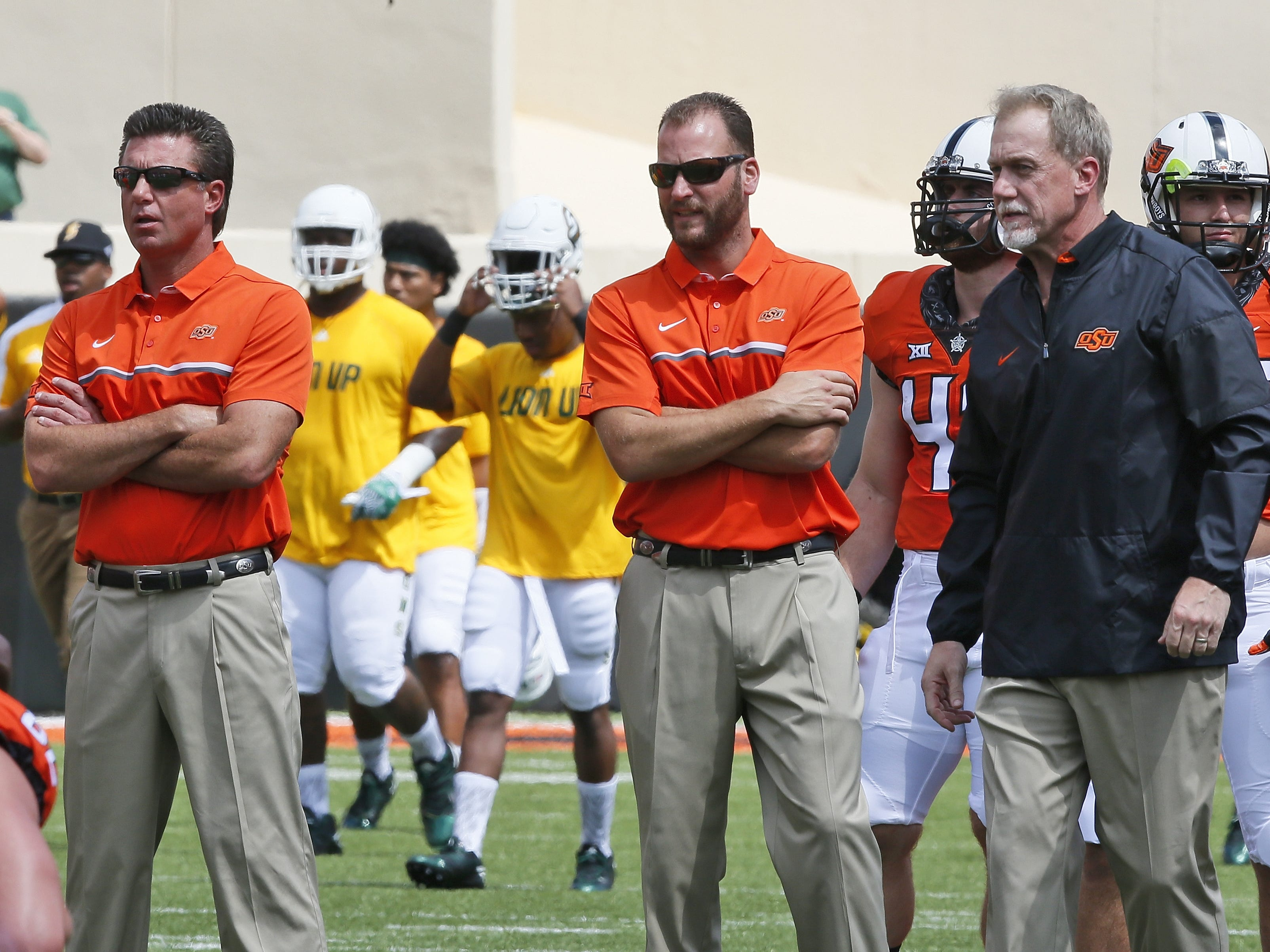In this Saturday, Sept. 3, 2016 photo, Oklahoma State head coach Mike Gundy, left, Mike Yurcich, center, Oklahoma State offensive coordinator, and  Glenn Spencer, right, defensive coordinator, watch warm-ups before an NCAA college football game against Southeastern Louisiana in Stillwater, Okla.