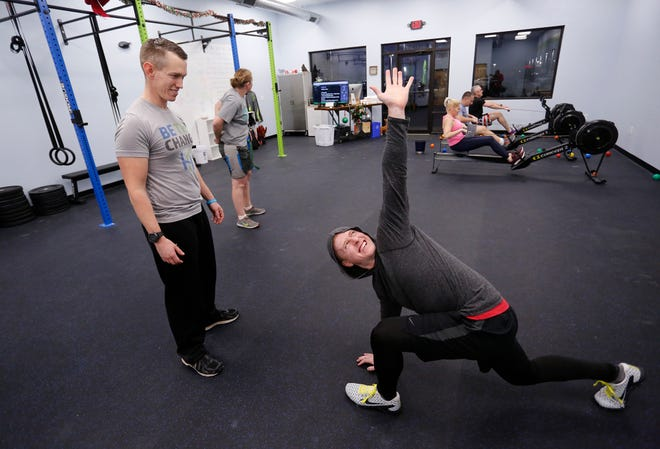 Movement coach Lucas Woody, left, looks on as Adam Kurtz performs a Spiderman with a twist, an exercise that helps increase range of movement, Monday, December 10, 2018, at Human Movement Performance and Prehabilitation, 3526 Osborne Drive in Lafayette.