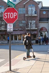 A student rides a BIRD electric scooter along the sidewalk at the corner of Columbia Street and Northwestern Avenue Tuesday, December 11, 2018, in West Lafayette. West Lafayette started towing the scooters Monday after complaints that they were clogging sidewalks.