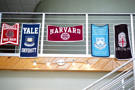 Flags of several universities are on display at T.M. Landry College Prep in December 2017.
