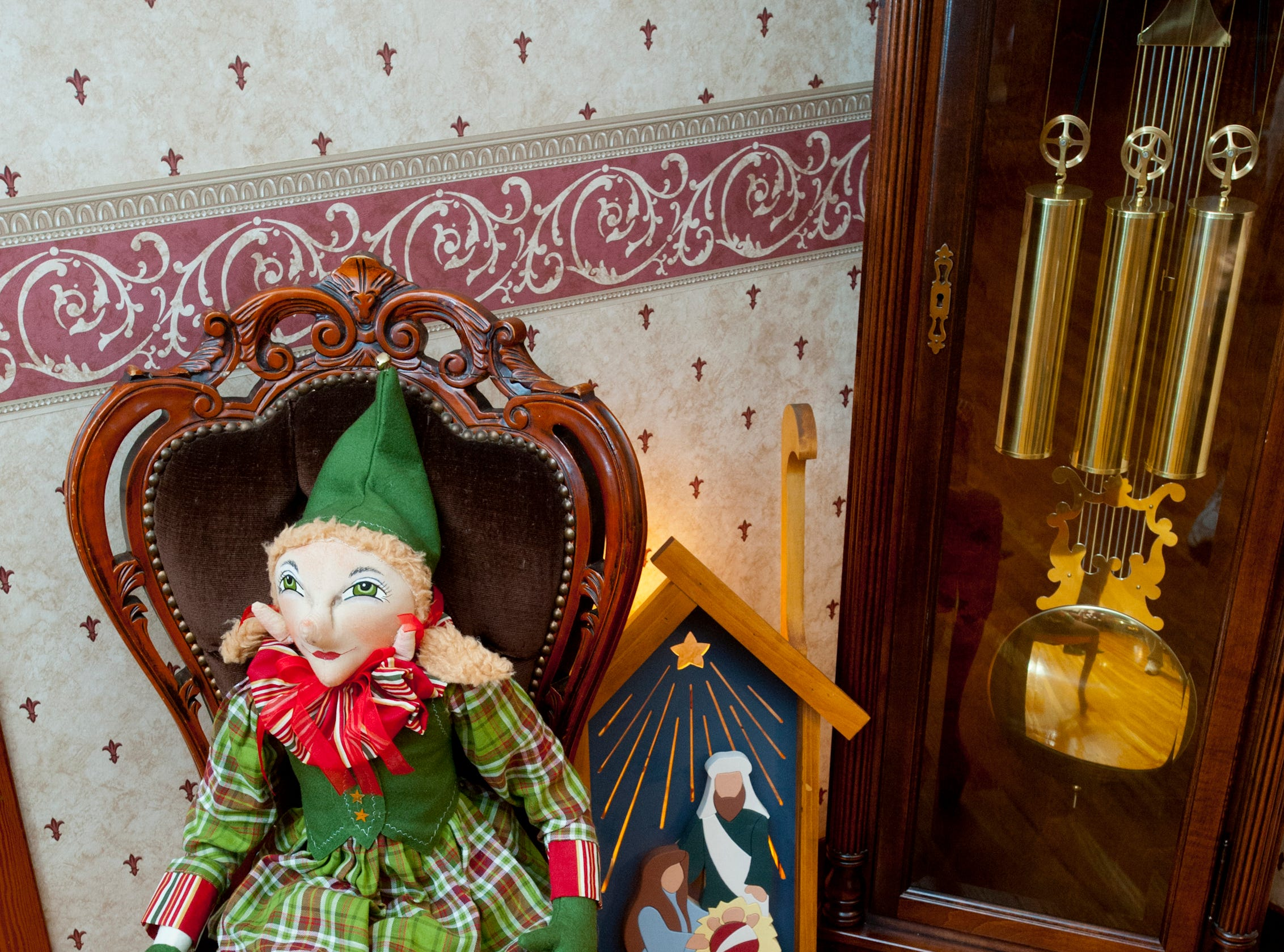 "This Joe Spencer ""Gathering Traditions"" elf named Helena was borrowed from a neighbor and sits next to a grandfather clock in the living room.