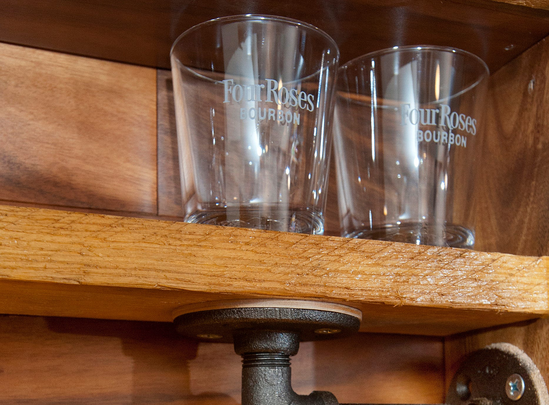 Bourbon glasses collected by the Cliffords are on display in the bourbon bar in their basement, built by Cliff Clifford using pipe fittings as shelf supports.