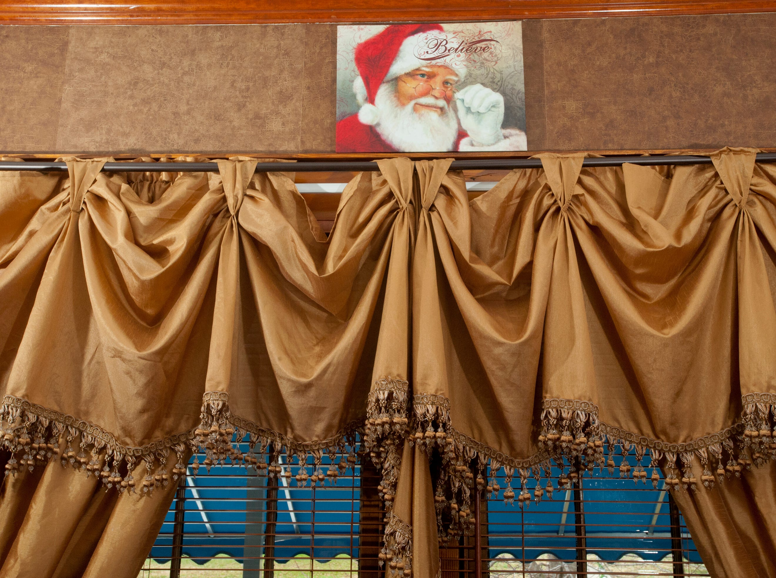 "A portrait of Santa with the word ""Believe"" is hung atop the drapes in the Clifford den.