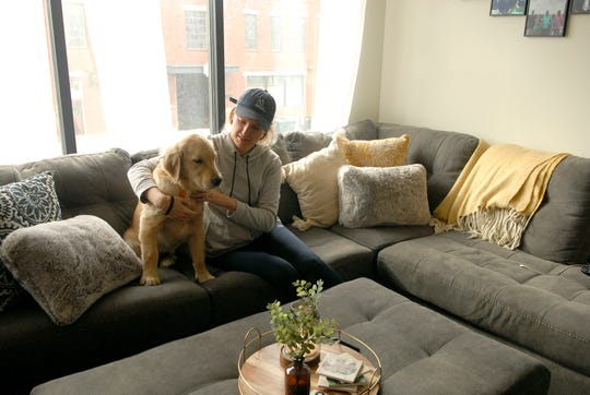Kaitlyn Kiely, 31, sits with her golden retriever Seven in the Main & Clay Apartments. Dec. 4, 2018
