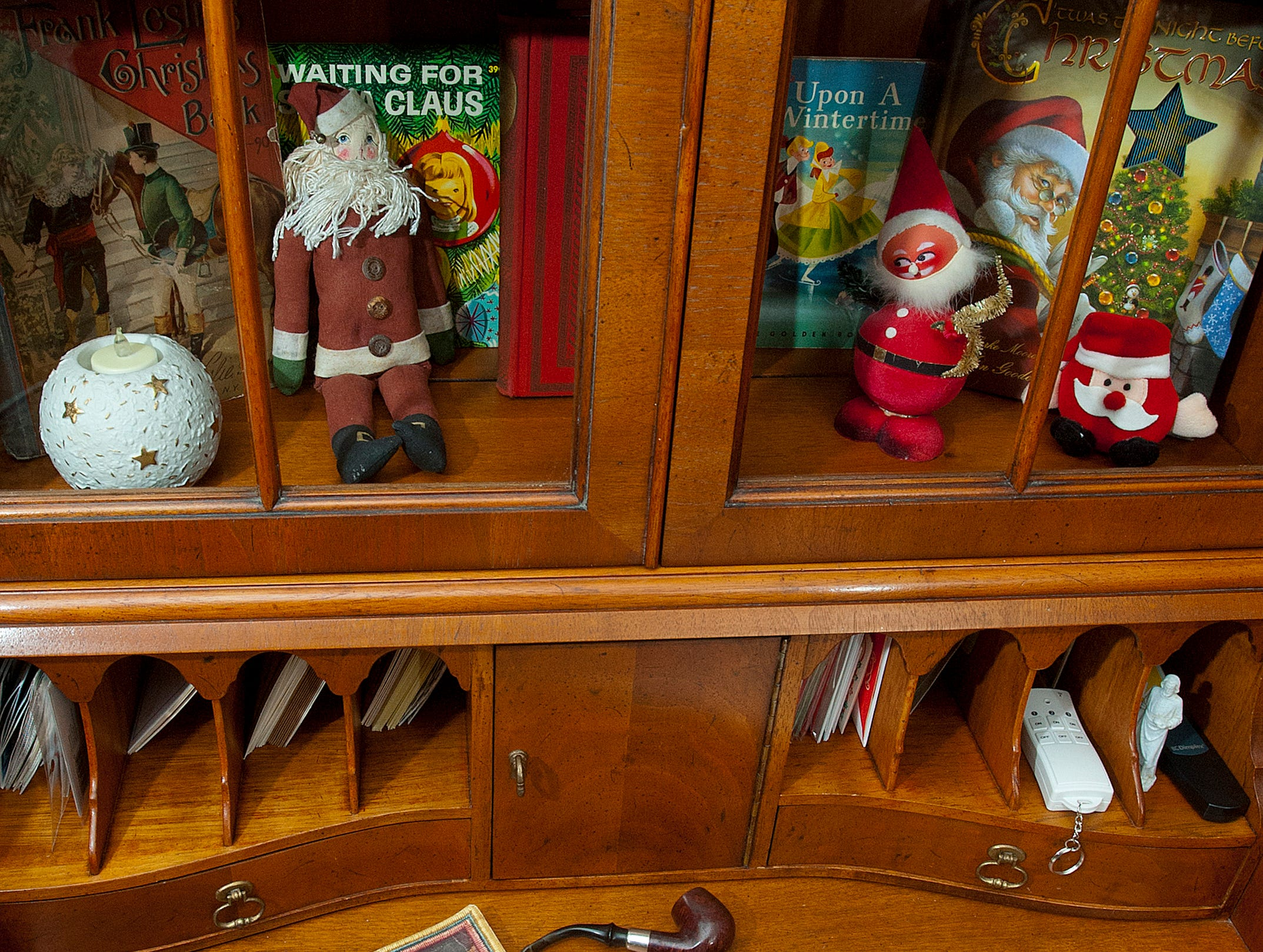 "The shelves of the ""Santa Room,"" are filled with Christmas and Santa story books and decorative items. Here, a book on Christmas, 1937, and a book on the 12 days of Christmas, sit atop the desk of a secretary.