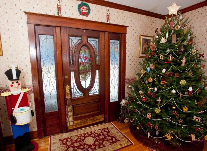The Clifford front door welcomes guests into the living room where a large nutcracker built by Chris Clifford, and a Christmas tree decorated with hand-crafted ornaments made by Chris are found.