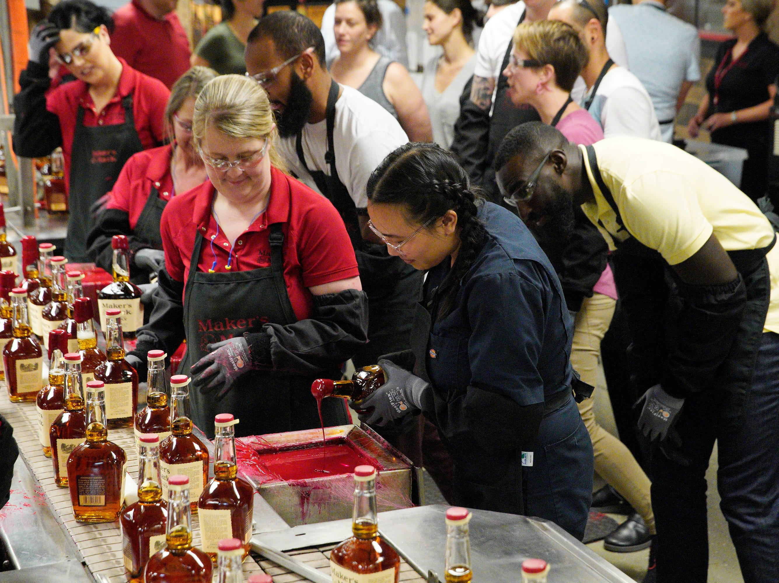 """Chef Nini Nguyen, center, dips a Maker's Mark bottle into red wax on episode 2  of """"Top Chef"""" season 16."""