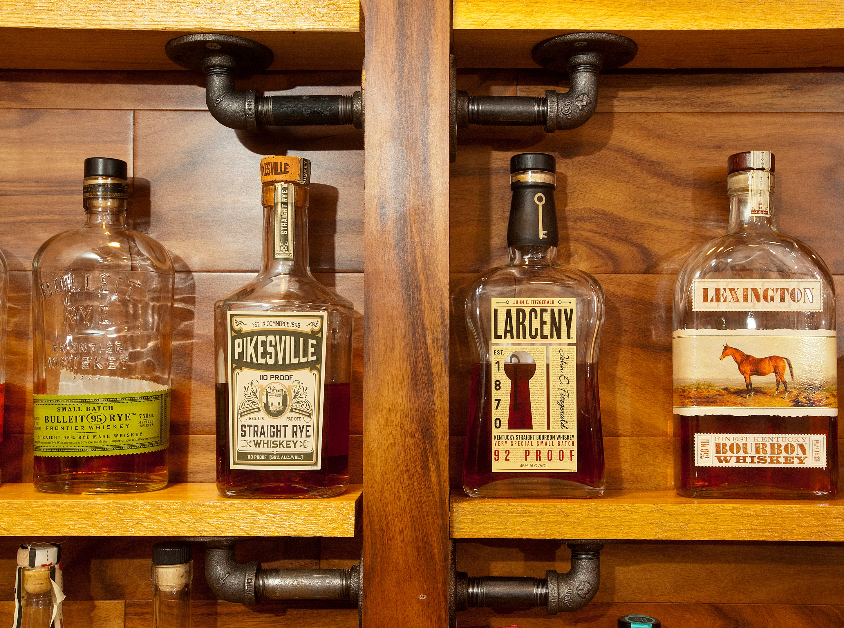 The Cliffords collect bourbon bottles on display in the bourbon bar in their basement, built by Cliff Clifford using pipe fittings as shelf supports. A bit of Larceny can be seen between the two bottles of whiskey, Pikesville and Lexington, named after Kentucky cities.