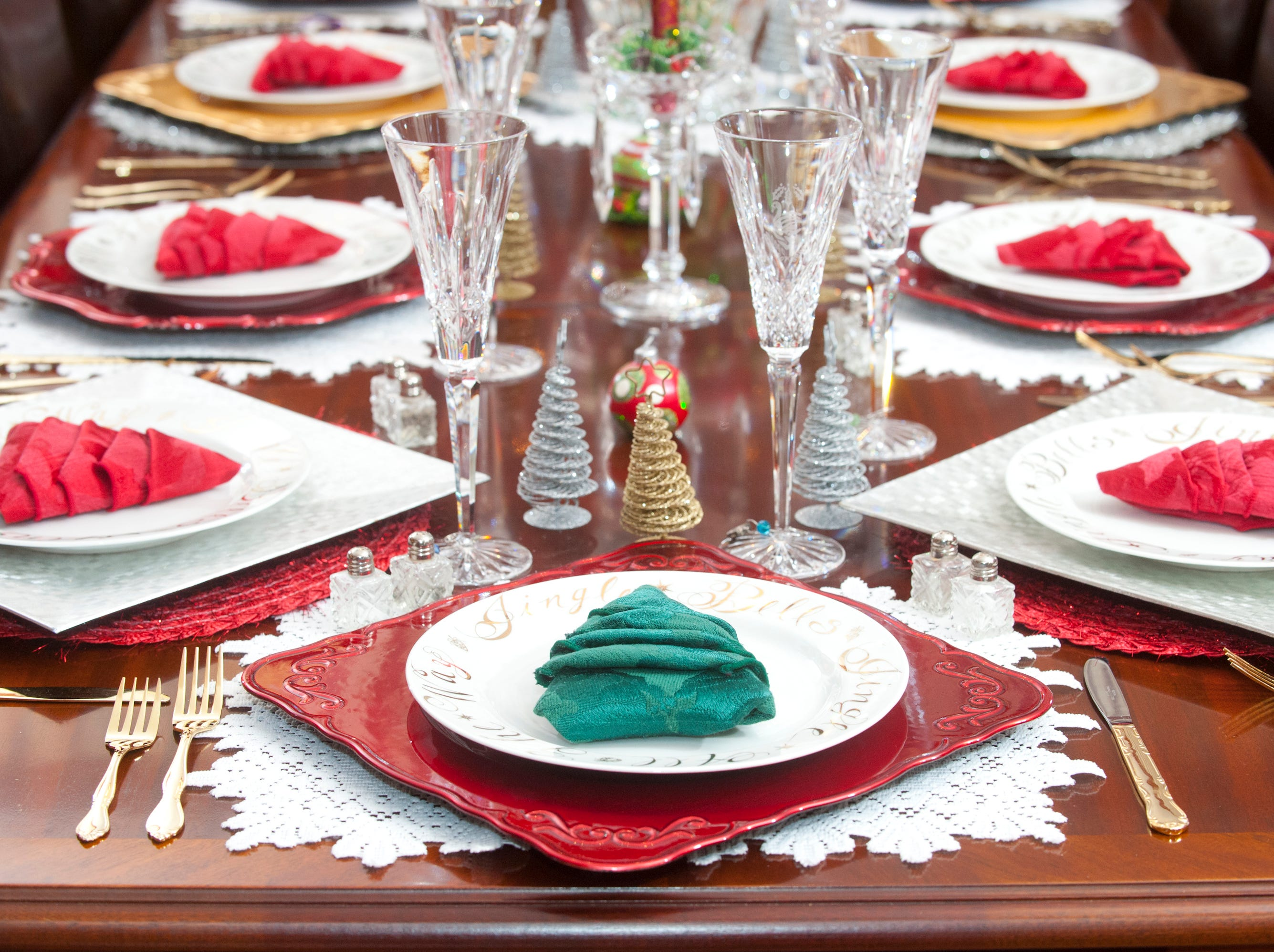 This twelve-piece dining table setting features napkins folded like Christmas trees. 