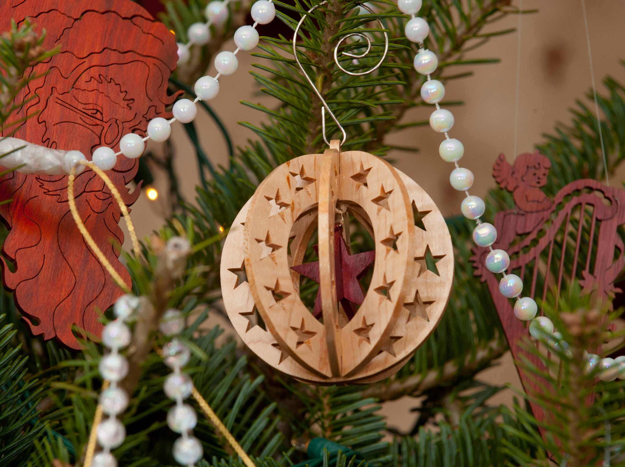 A handmade Christmas ornament made by Chris Clifford, from unstained natural wood.
