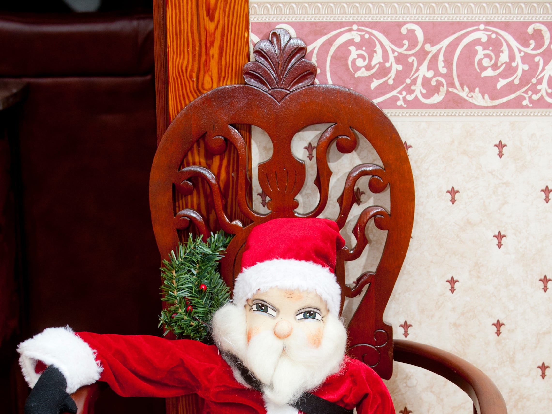 "This Joe Spencer ""Gathered Traditions"" Santa, named Jonas, sits comfortably in a living room chair.