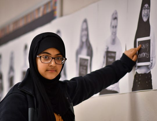 """Seba Aldhamen,  a junior at Bath High School, points to her portrait that is part of """"The Chalkboard Project."""" The project was started by Spring Lake art teacher Jennifer Gwinnup and adopted by Bath High School.  Students write down names they've been called, or things they've been told onto a chalkboard and have their portrait taken. The pictures are printed and hung throughout the school. Later in the week, sticky notes are put over the chalkboard portion, and the text is replaced by their peers with some of the positive traits fellow-students see in them."""