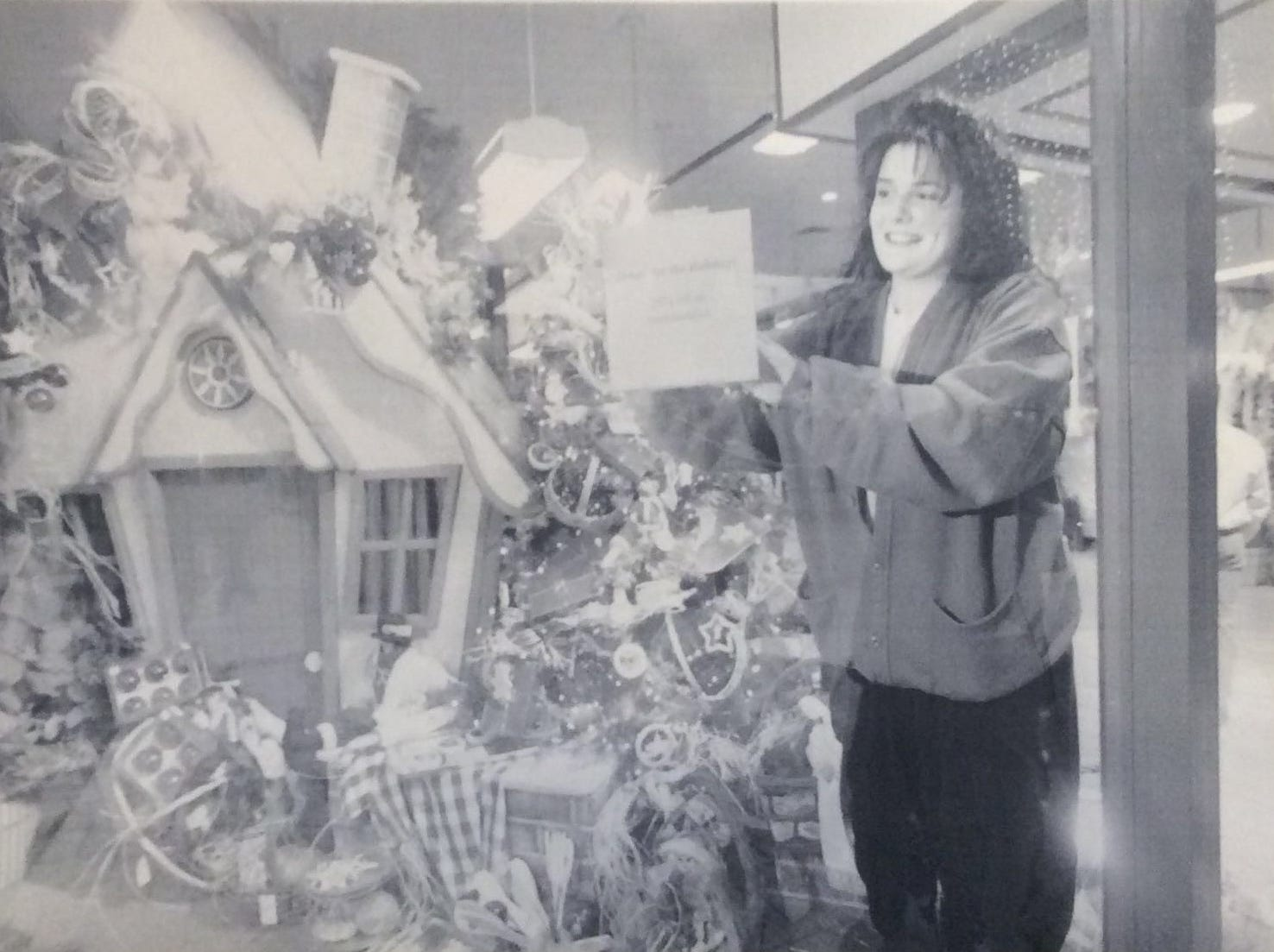 Gwen Lawson, manager of the Lansing Mall store Home for the Holidays, displays a sale sign announcing 25% off all merchandise, December 1994.