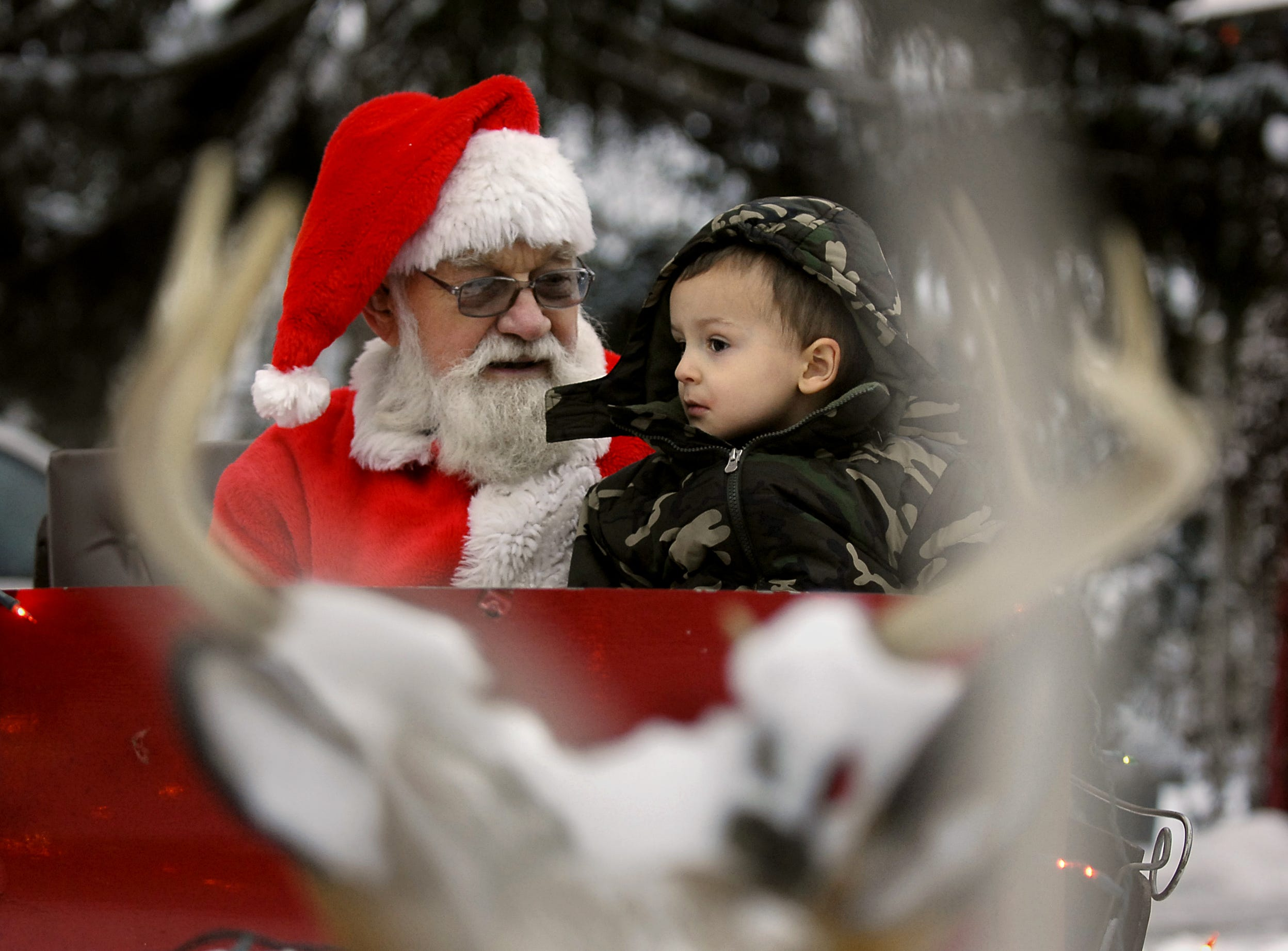 Reece Bowman, 3, tells Santa what he would like for Christmas. Emil Kletke sits out front his house in a sleigh so kids can have their photo taken with Santa Claus, Dec. 17, 2008.