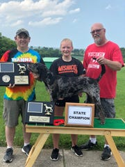 The Wisconsin State Youth Championship Coon Hunt was sponsored by the Wisconsin Coon Hunters Association and hosted by the Sugar River Coon Hunters. This competition was held at the Brookland Sportsmen's Club on June 16. Emily Paplham, 17, of Mishicot, handled her own dog, an American Leopard Hound GRCH (Grand Champion) Born on The Bayou, and won Grand Champion Female and Overall Champion. Pictured from left: Jay Lahey, judge and master of hounds; Emily Paplham; and her father David Paplham.