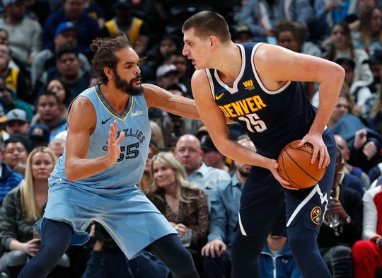 Denver Nuggets center Nikola Jokic, right, looks to pass the ball as Memphis Grizzlies center Joakim Noah defends in the first half of an NBA basketball game Monday, Dec. 10, 2018, in Denver. (AP Photo/David Zalubowski)