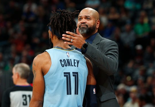 Memphis Grizzlies head coach J.B. Bickerstaff, back, consoles guard Mike Conley as the Denver Nuggets take the lead in the second half of an NBA basketball game Monday, Dec. 10, 2018, in Denver. The Nuggets won 105-99. (AP Photo/David Zalubowski)