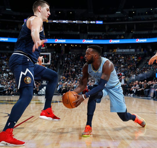 Memphis Grizzlies guard Shelvin Mack, right, looks to pass the ball as Denver Nuggets center Nikola Jokic defends in the first half of an NBA basketball game Monday, Dec. 10, 2018, in Denver. (AP Photo/David Zalubowski)