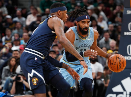 Memphis Grizzlies guard Mike Conley, right, drives up the court past Denver Nuggets forward Torrey Craig in the first half of an NBA basketball game Monday, Dec. 10, 2018, in Denver. (AP Photo/David Zalubowski)