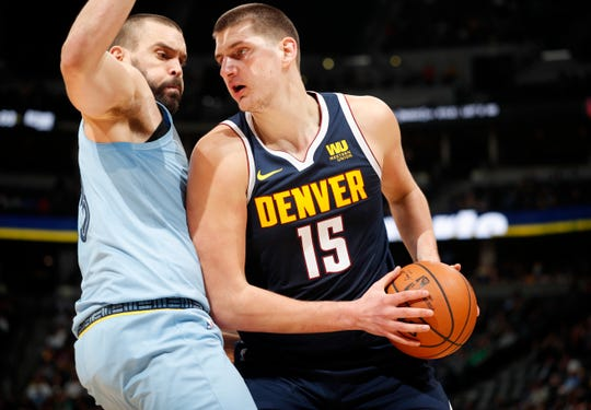 Denver Nuggets center Nikola Jokic, right, goes up for a basket as Memphis Grizzlies center Marc Gasol defends in the second half of an NBA basketball game Monday, Dec. 10, 2018, in Denver. The Nuggets won 105-99. (AP Photo/David Zalubowski)