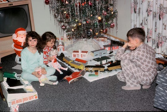 "It's Christmas morning 1963 for the Plunkett family in Milwaukee. From left, Meredee, Becky, and Scott Plunkett linger with their gifts, though Scott's focus seems to be the train under the tree. This photo was one of many like it in Classic Toy Trains special 2018 issue ""Christmas and Electric Trains,"" published by Kalmbach Media."
