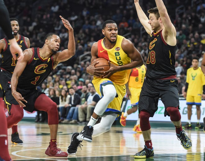 Bucks guard Sterling Brown drives for the basket between the Cavaliers' Rodney Hood and guard Matthew Dellavedova.