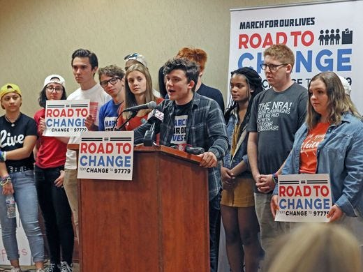 """Alfonso Calderon, 16, a student at Marjory Stoneman Douglas High School, speaks June 22 at a rally in Janesville. David Hogg (third from left holding """"Road to Change"""" sign, another Douglas High student also spoke at the rally. Students were calling for stricter gun-control laws."""