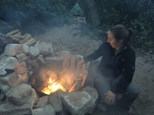 Milwaukee Journal Sentinel reporter Chelsey Lewis tends to a fire at a campsite in Rock Island State Park.