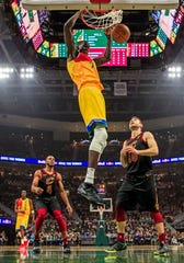 Bucks forward Thon Maker throws down a two-handed dunk against former teammate Matthew Dellavedova and the Cavaliers on Monday night.